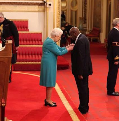Photo: Queen Elizabeth presents MBE to Chukwu-Emeka Chikezie at Buckingham Palace