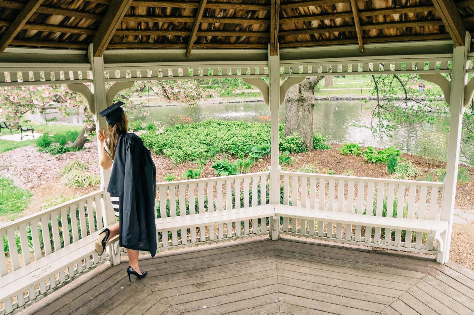Graduate in a gazebo overlooking a pond.
