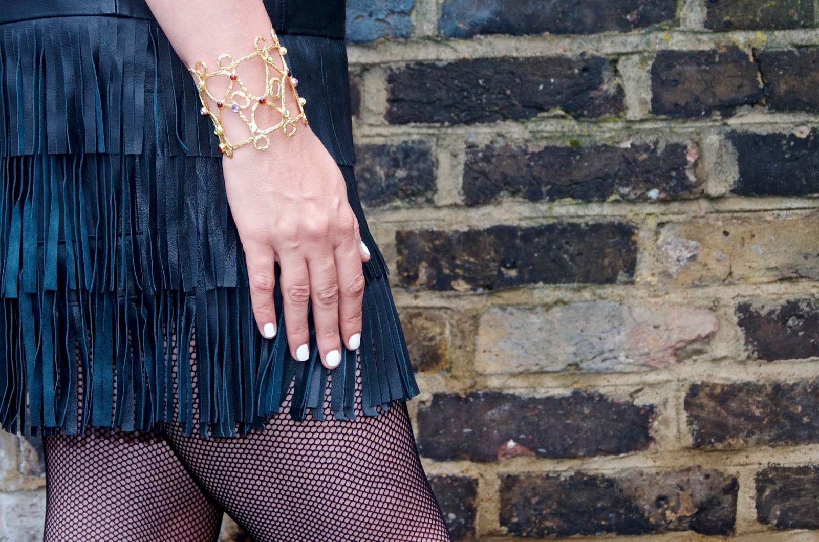 white nails, black leather fringe, fishnets, gold cuff