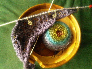 A cake of purple-to-red gradient yarn and an asymmetrical knitted lace triangle, still on the needles.  3 silver rose stitch markers are hooked into the lace.  Both the yarn cake and the lace are inside a wooden yarn bowl.