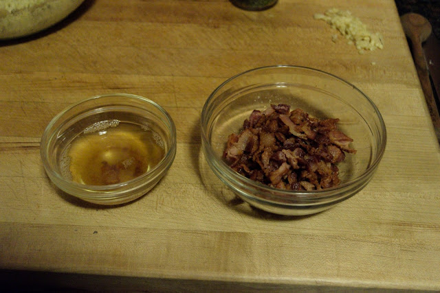 The browned bacon in a glass bowl and the rendered bacon fat in another glass bowl on a cutting board.