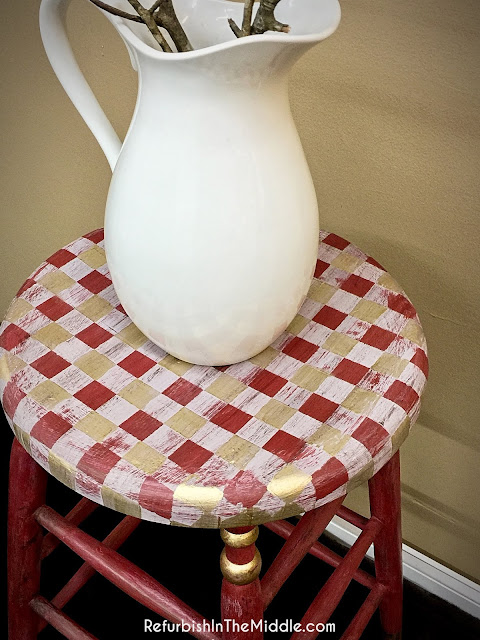white ceramic pitcher on a decorative tall red wood stool, accented with buffalo check seat