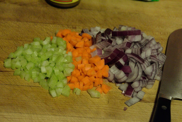 Celery, carrot, and onion, diced on the cutting board.
