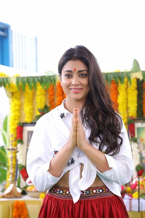 Shriya Saran looks Smiling Beautiful in White Shirt and Red Skirt
