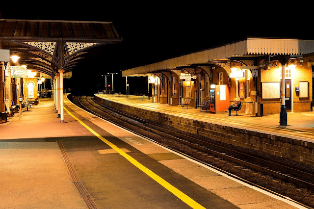 One solitary passenger waits for a train oblivious to the beauty of the iron filigree metal work in this late night photo of Wellingborough station