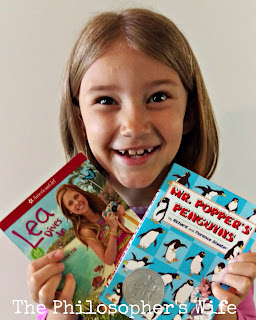 A girl with a wide grin is holding two books: Lea Dives In and Mr. Popper's Penguins.