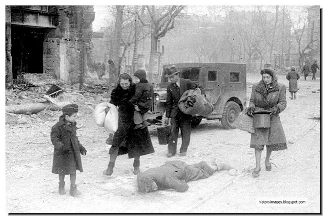 German women walk past dead soldier 1945