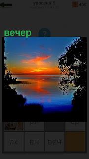 наступил вечер и солнце склонилось в закате над водоемом