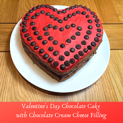 a red heart shaped chocolate sandwich cake decorated with chocolate chips