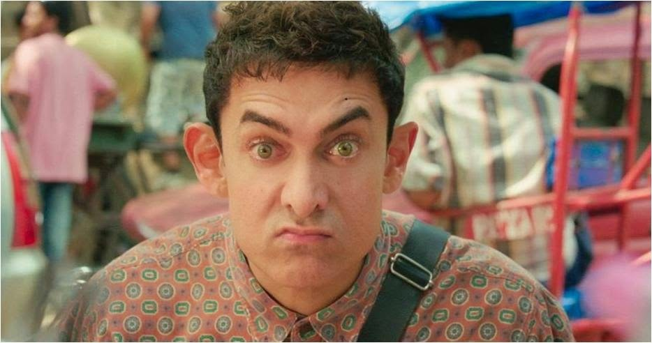 Aamir Khan in PK looks with flat hair, raised eyebrows, wide green eyes, popped ears and colorful cloths in a movie still