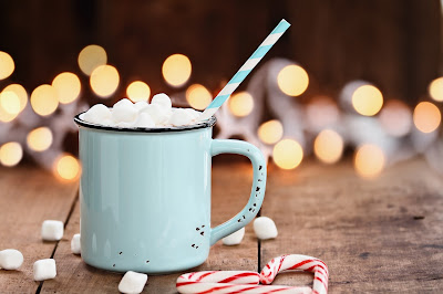 Cup of cocoa in a mint colored mug with a stray and marshmellows with holiday lights flickering in the background and marshmellows on the table and canycanes