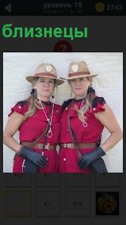 Две девушки одинаковы одеты и похожие друг на друга как близнецы