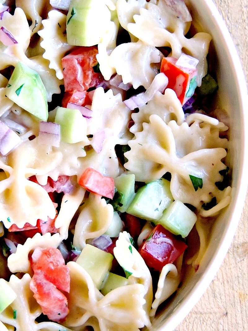 Mediterranean Pasta Salad in a bowl with a green striped hand towel in the background on a wooden background