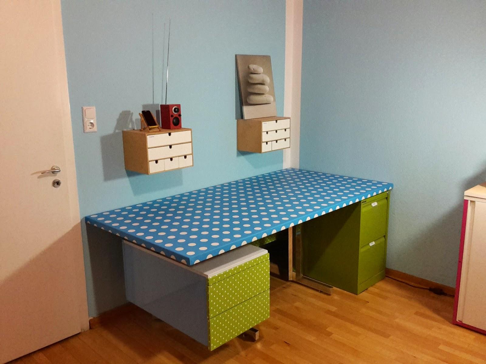 Bild des Schreibtischs. Blau bespannt mit weißen Tupfen. Hellblauer Kasten. Froschgrüne Schubladen mit weißen Tupfen. Froschgrüner Bisley.