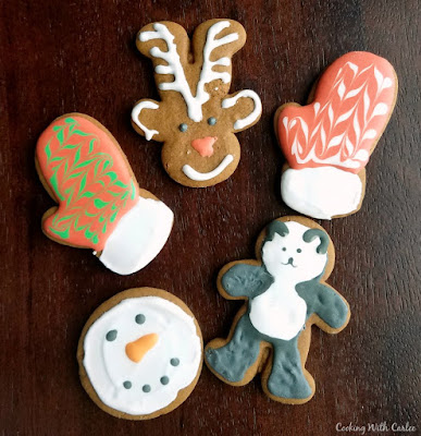 German gingerbread cookies decorated as rudolph the red nose reindeer, mittens, a panda and a snowman face