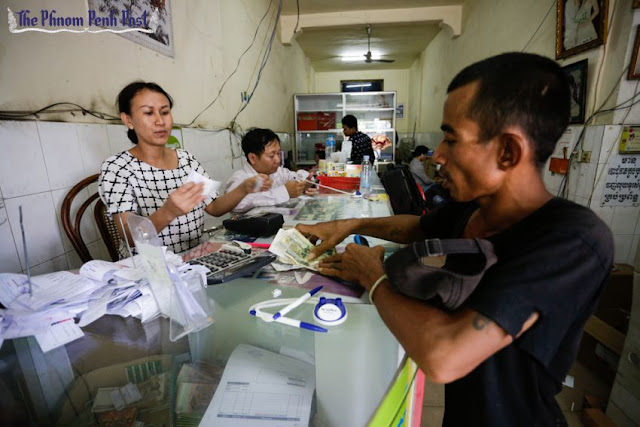 A man receives money from a Wing agent after concluding a transaction at a Phnom Penh branch yesterday afternoon. Hong Menea