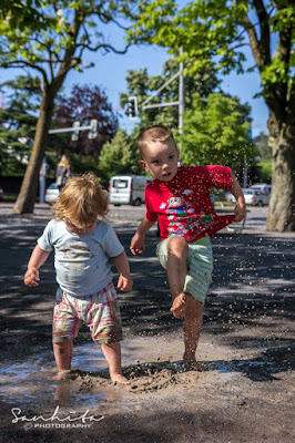 Two babies jumping and enjoying the muddy puddle