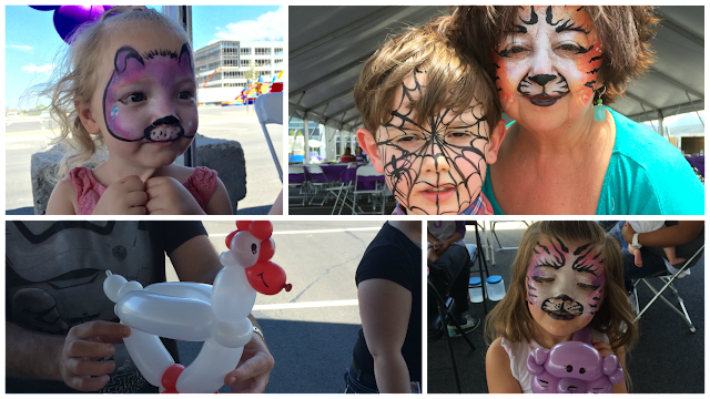 A young girl with her face painted like a puppy. A Grandma and her grandson with their faces Painted. A Balloon Chicken. A Young girl with her balloon cat and her face painted like a cat.