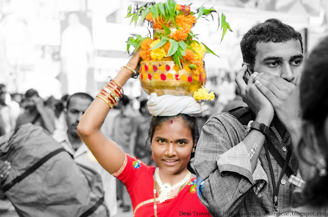 a smiling women carrying bonalu at ujjaini mahakali temple