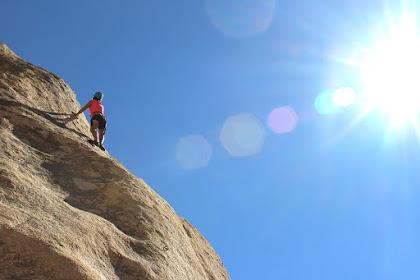 Pria yang mendaki gunung yang miring