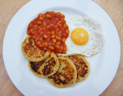 Scottish Tattie Scones on a white plate with baked beans and a fried egg