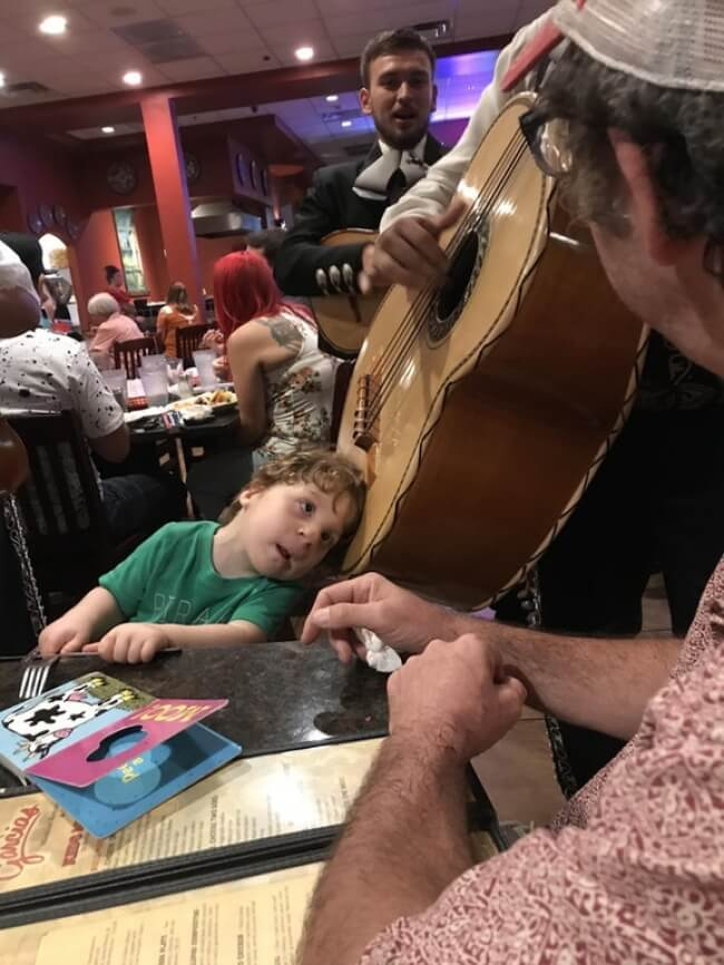 15 Powerful Pictures That Will Make Your Day - A musician let this hard-of-hearing little boy put his head on the guitar so he could hear it.
