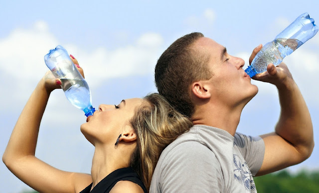 A man and a woman drinking water from a water bottle. Woman on left and man on right back to back.