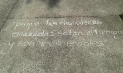 """pintada en el suelo con una cita de O. Paz: """"porque las desnudeces enlazadas saltan el tiempo y son invulnerables""""."""