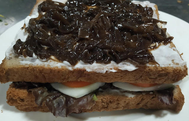 Caramelized onions spread over layered bread slices for veg club sandwich recipe