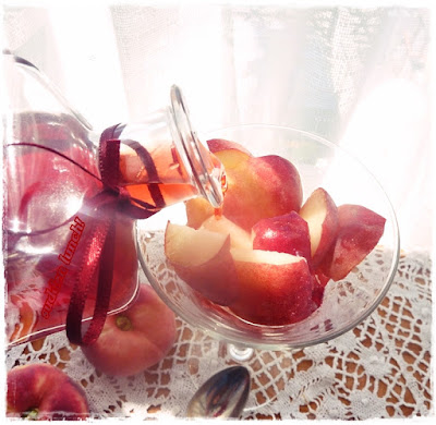pouring raspberry vinegar over a glass of peaches