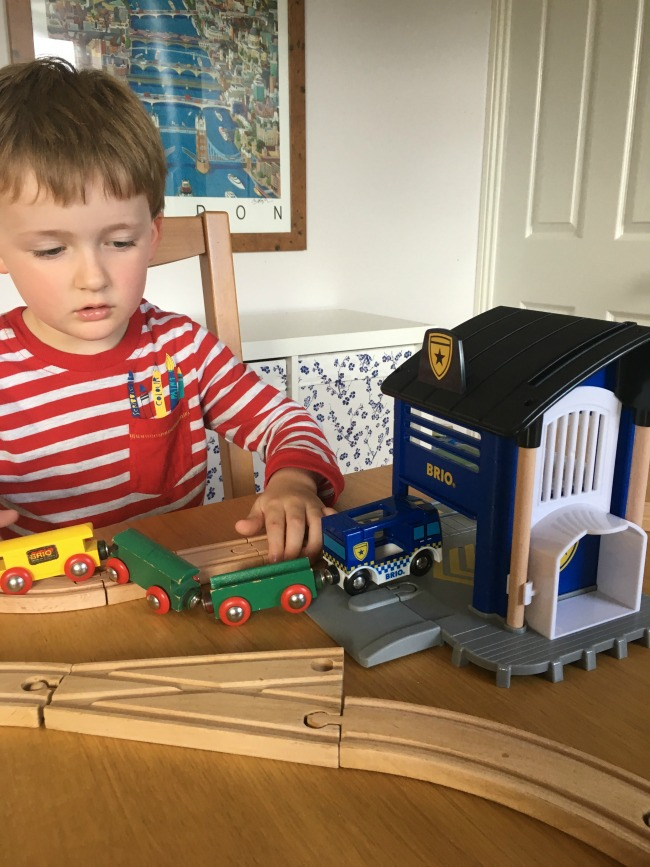 boy-playing-with-Brio-police-car-and-policeman-figure-with-older-version-of-brio