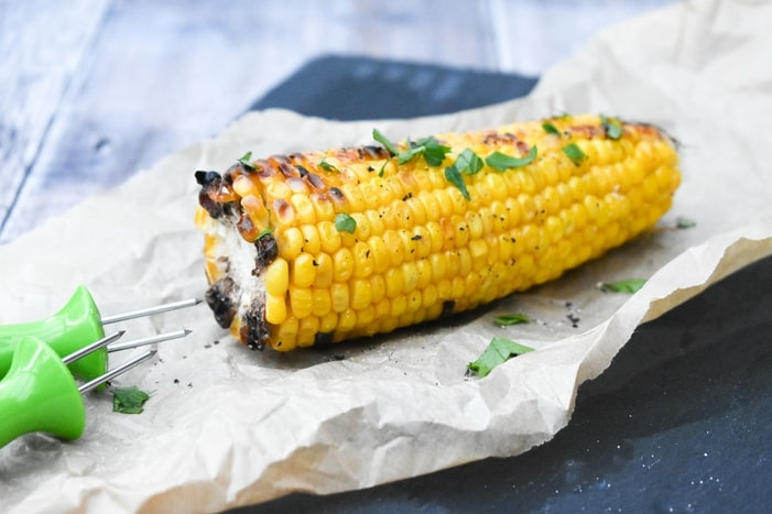 grilled corn on the cob with seasoning and fresh herbs