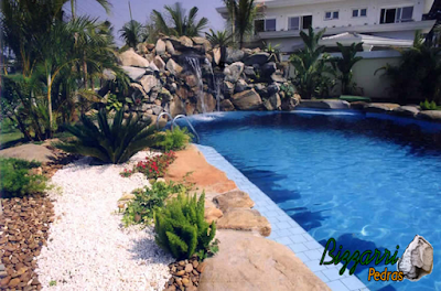 Detalhe da cascata de pedra na piscina com pedras ornamentais com os detalhes da colocação das pedras ornamentais na borda da piscina com execução do paisagismo.