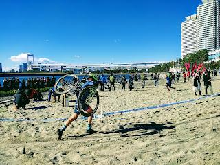 自転車を担いでお台場の砂浜を駆け抜ける選手