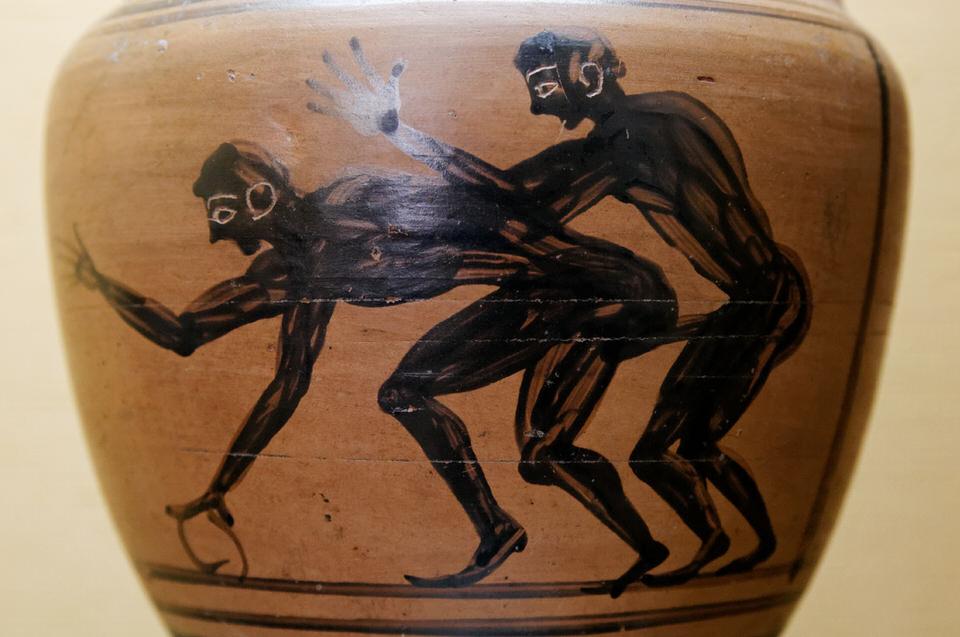 Δύο νέοι που κάνουν σεξ, ένας από τους οποίους κρατάει ένα στεφάνι. Λεπτομέρεια από έναν αμφορέα