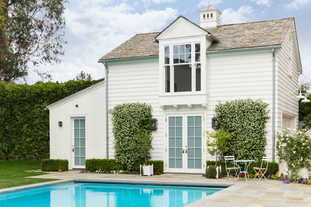 Exterior of white pool house studio at traditional California home