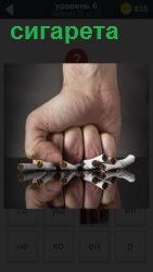 мужской кулак раздавил несколько сигарет на столе