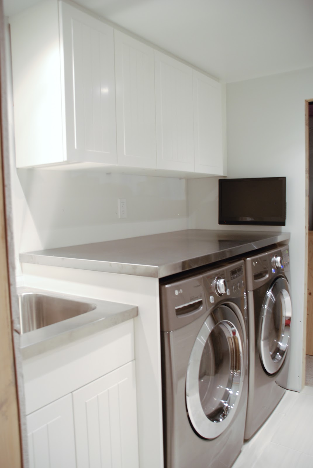 stainless steel countertop in laundry room, floating countertop in laundry room, counter over front load washer and dryer