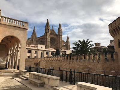 castle and cathedral in palma under a cloudy sky