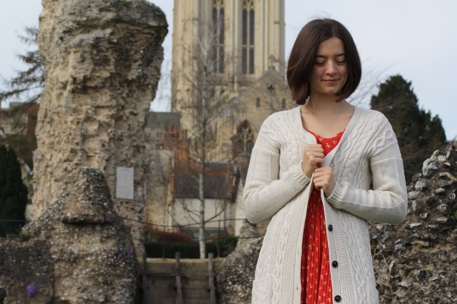 Abbey, wearing a red dress and knit cardi, stands in front of the ruins of Bury St Edmunds Abbey with the cathedral in the background