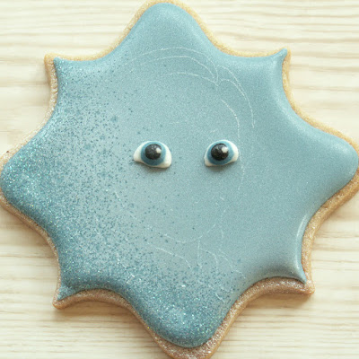Outline of Anna scribed onto cookie, and royal icing eyes attached, cookie and photo by Honeycat Cookies