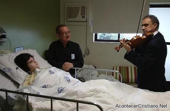 Violinista tocando ante enfermo en hospital