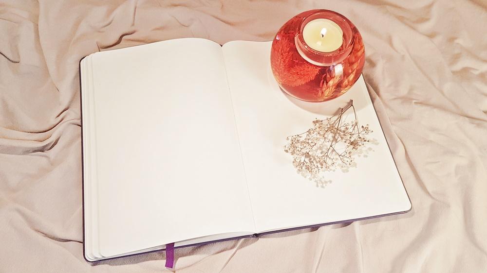 Aufgeschlagenes Buch mit Kerze und Blume