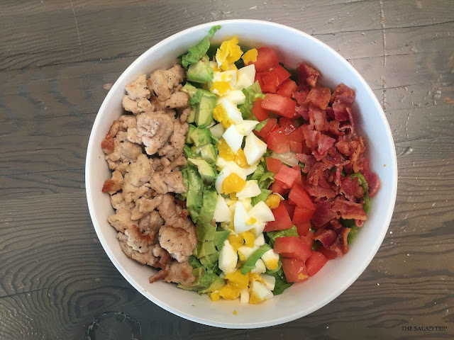 White bowl on wooden table with ground chicken, avocado, hard boiled eggs, tomatoes, bacon and romaine