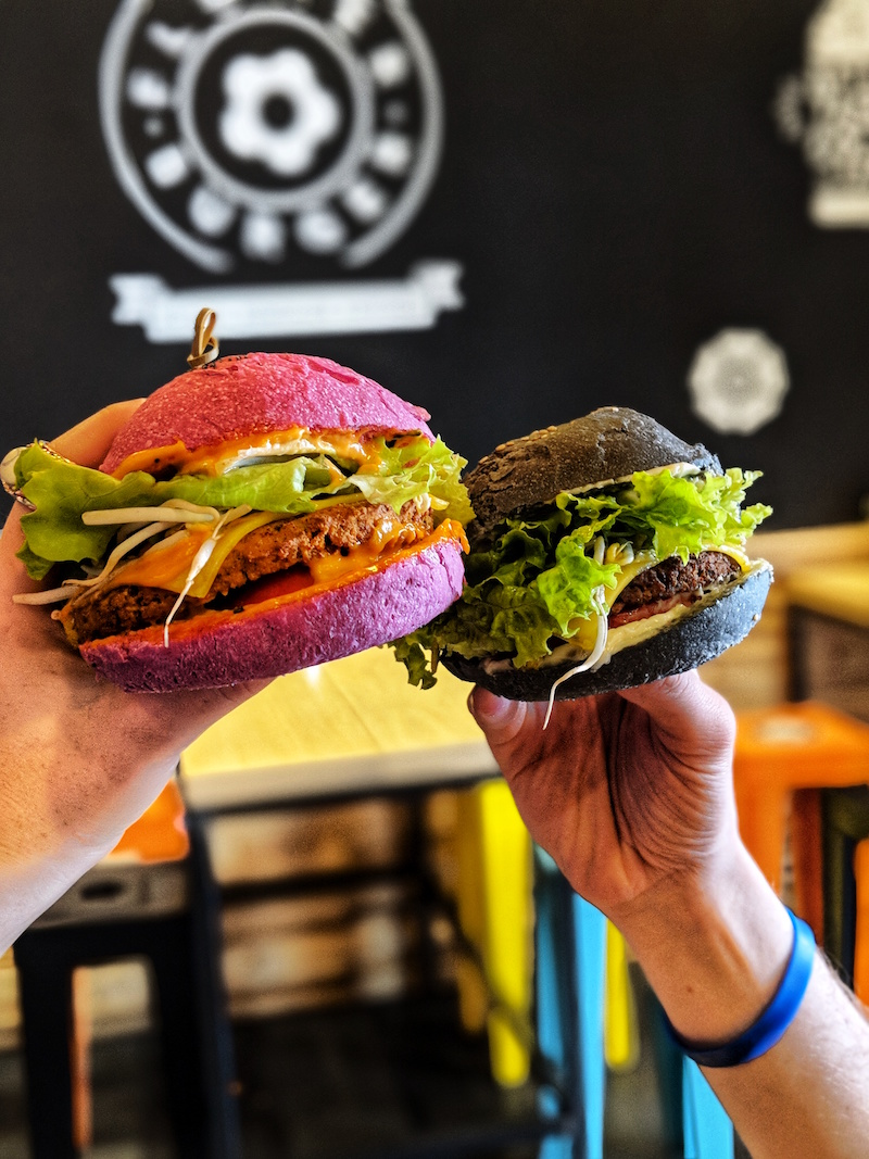 The Cherry Bomb burger with a pink bun and the Flower Burger with a black bun in Rome