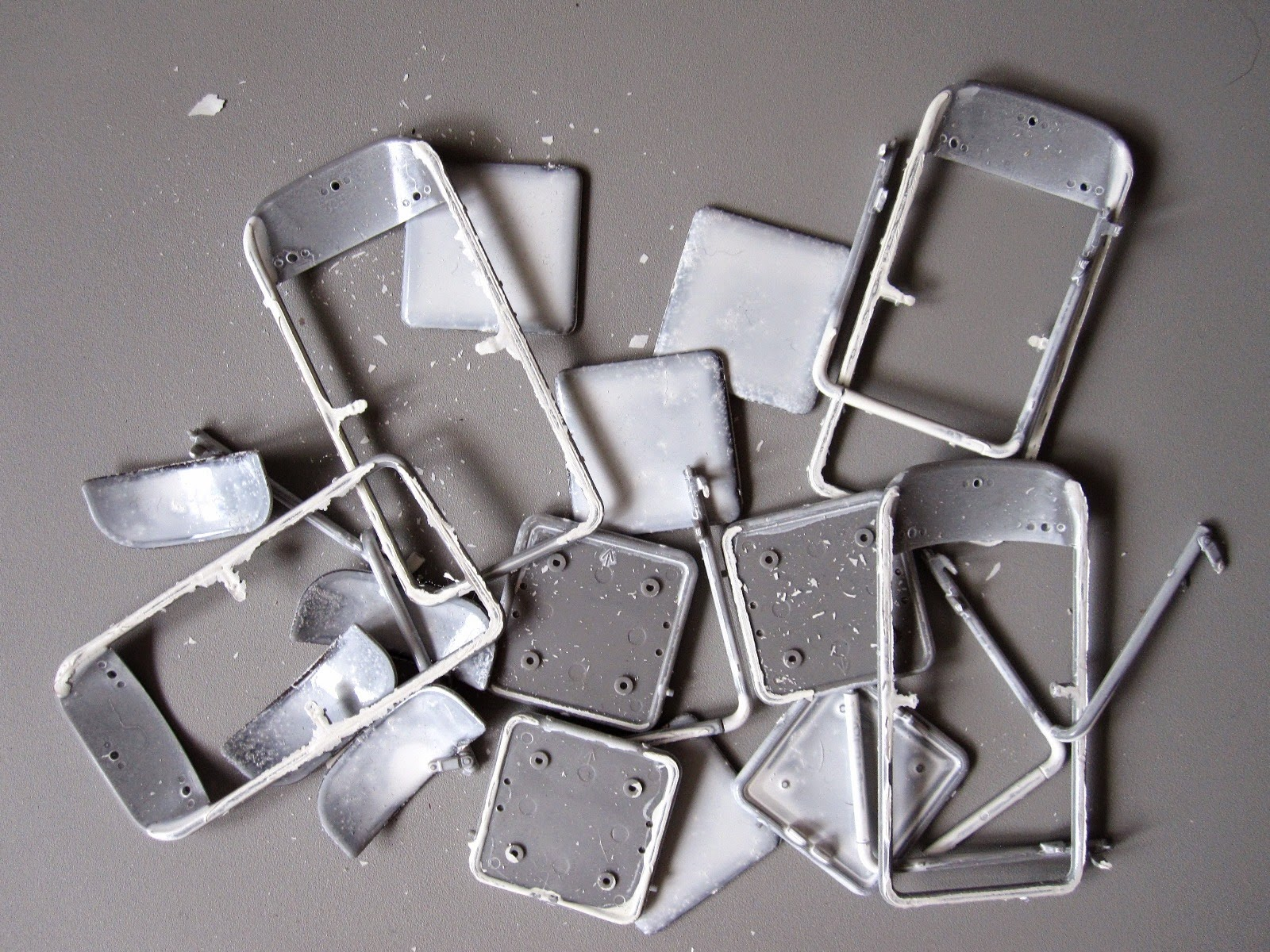 A pile of partly-painted modern dolls' house miniature folding chair kit parts.