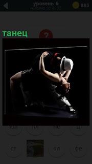 Мужчина и женщина в костюмах исполняют танец похожий на танго