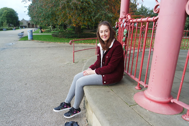 Lyd is sat on the bandstand in the park wearing grey jeans and a burgundy jacket
