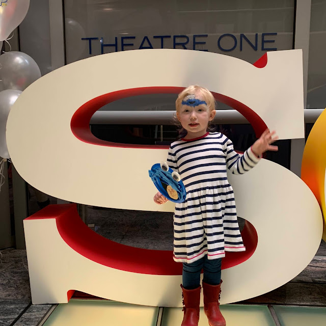 A toddler standing in front of the S of Sony with Cookie Monster face paint on and Cookie Monster decorated plate puppet