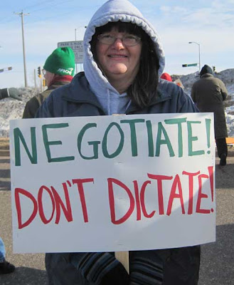 Woman with a sign reading Negotiate! Don't Dictate!